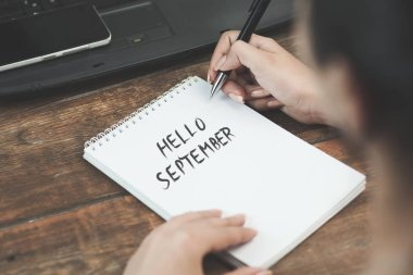 Woman written hello september text on notepad with keyboard on table stock vector