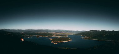 Panoramic view of mountains surrounding bay of water