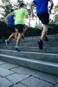 Alacsony, szög, kilátás a három hivatásos férfi sportolók futva lépcsőház park naplementekor