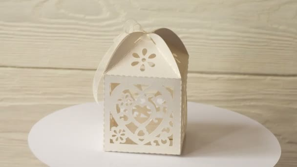 White vintage paper box for gifts turns on a stand against a white wooden wall
