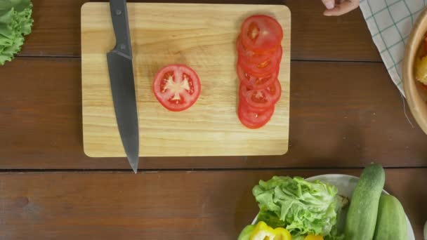 Top view of woman chief making salad healthy food and chopping tomato on cutting board in the kitchen