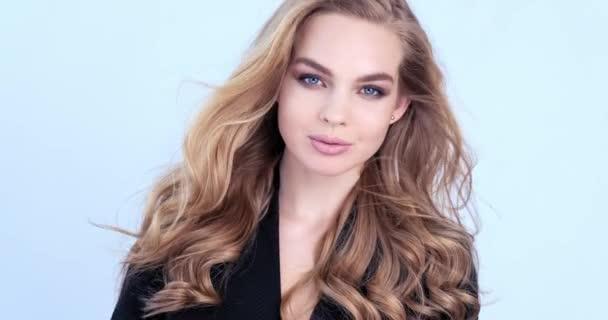 Gyönyörű, fiatal szőke nő hosszú hajjal. Divatmodell néz a kamerába. Lenyűgöző arca van egy fehér lánynak. Szexi modell gyönyörű kék szemekkel. Lassú mozgás. Szépség koncepció. 4k felvétel.