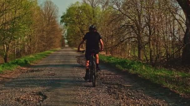 Zpomalený pohyb - Mladý muž cyklista jezdí na venkovské silnici. Teenager na horských kolech, v přírodě. Muž v helmě na kole šlapání na černém kole na asfaltové silnici, pohled zezadu.