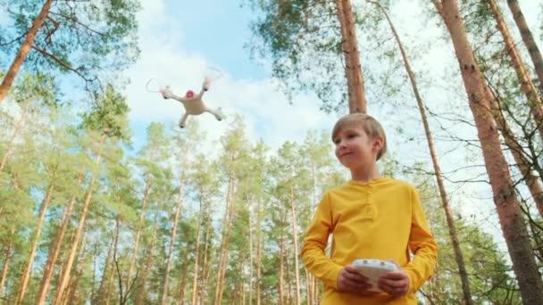Kind startet die Drohne im Freien. Junge spielt mit Quadrocopter in der Natur Ein weißer Junge lernt im Park, eine Drohne zu steuern. Zeitlupenvideo.