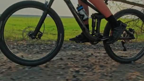 Zpomalený pohyb pánských nohou otáčí pedály horského kola. Detailní záběr kola, které jede na štěrku. Sledování pohybu kola. Cyklista šlape pedály na kole. Kolo