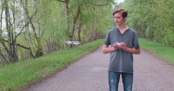 Junge hebt die Drohne mit der Fernbedienung an. Teenager startet Drohne im Freien Junger Mann spielt in der Natur mit einem Quadrocopter. Weißer Junge lernt in einem Park, eine Drohne zu fliegen. Zeitlupenvideo.