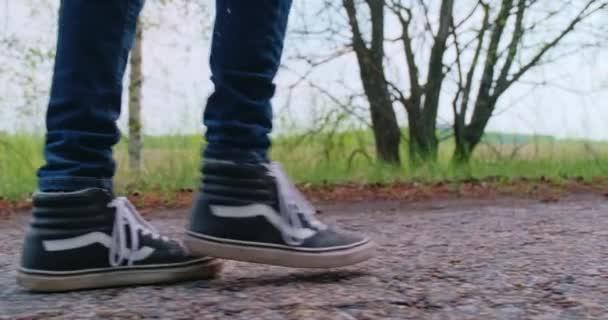 Legs Man Walking On Road. Man Legs Walking On Park. Seitenansicht Teenager-Beine auf Turnschuhen beim Gehen.