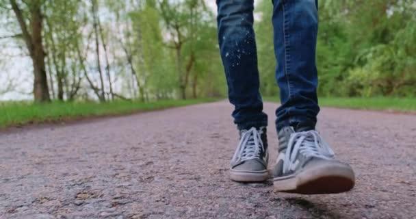 Legs Man Walking On Road. Man Legs Walking On Park. Teenie-Beine auf Turnschuhen.