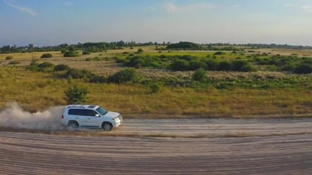 SLOW MOTION. AERIAL VIEW in Verbindung setzen. Weiße Geländewagen sind schnell unterwegs auf der Landstraße. Drohne verfolgt ein Auto, das im Gelände mit einer riesigen Staubwolke unterwegs ist. Rasant fahrendes Auto, das Staubwolken hinterlässt