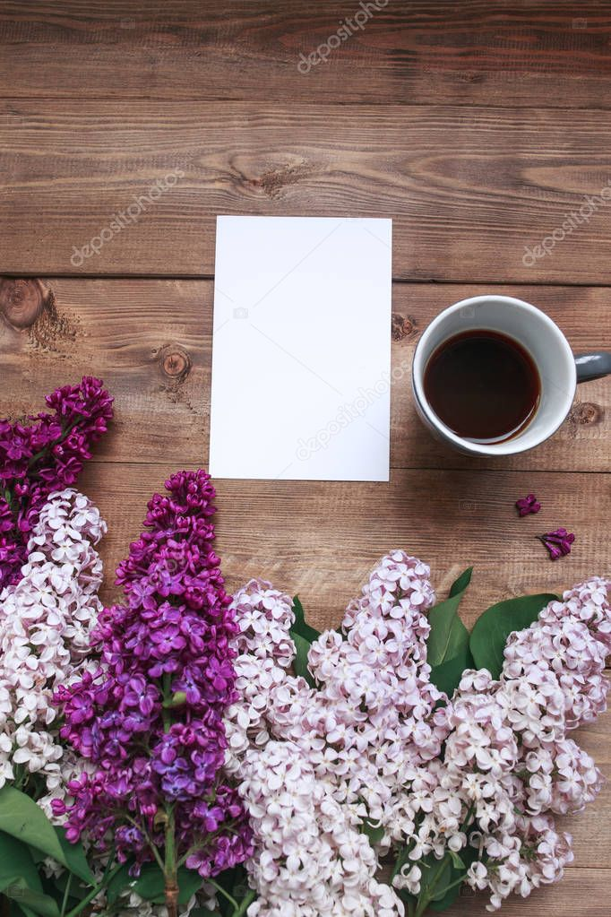 Bouquet of lilac flowers on wooden planks with blank card for text and coffee