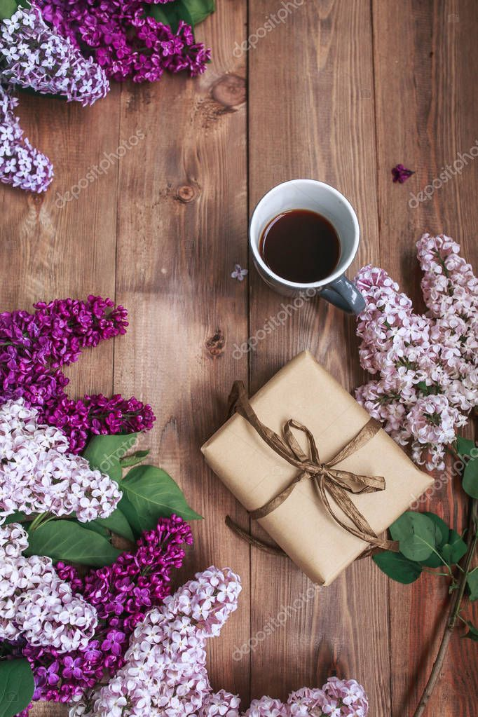 Bouquet of lilac flowers on wooden planks with gift and coffee.