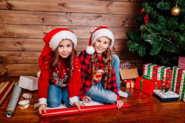 Happy funny little sisters in Santa hats pack gifts near Christmas tree