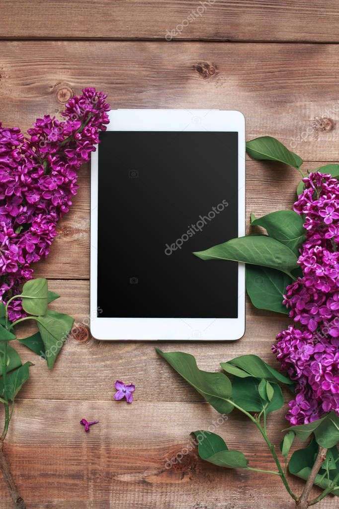 Bouquet of lilac flowers on wooden table with tablet. Top view