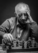 Idősebb ember sakkozik. Fekete-fehér