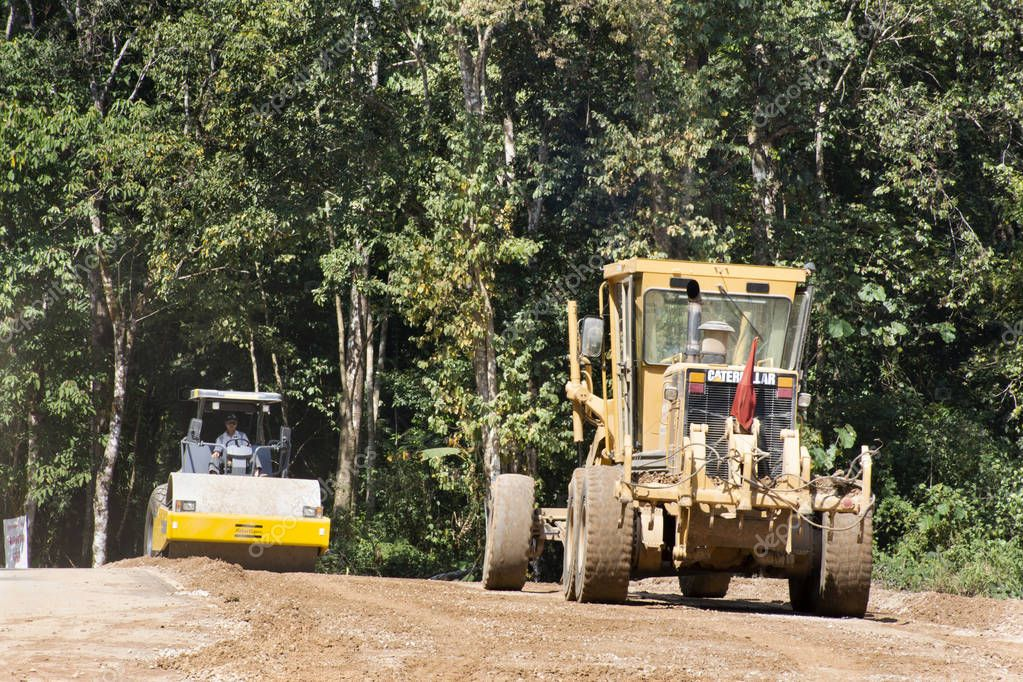 Asian thai workers use heavy machinery motor grade and vibratory roller working made and build road at Doi Tung mountain on February 22,2018 in Chiang Rai, Thailand