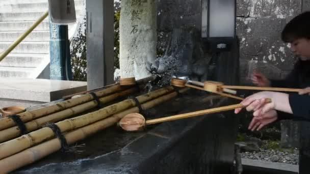 TOKYO, JAPAN - MARCH 31 :  People washing hand rite or Mitarashi ritual with Chozusha or Holy water in stone basin at Naritasan Shinshoji or Narita Temple st Chiba on March 31, 2019 in Tokyo, Japan