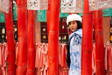 Travelers thai women wearing indigo shawl travel visit and take photo with red torii in Wat Phu Sa Ma temple in Ban Kung Mai Sak village at Pai city on February 28, 2020 in Mae Hong Son, Thailand