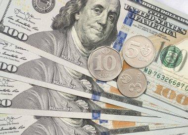Kyrgyzstan som coin on top of dollar bills