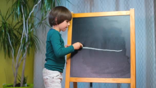Cheerful child draws on the blackboard with chalk