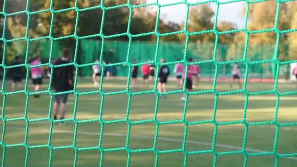 Nahaufnahme eines Sportnetzes. Im Hintergrund spielen sie Fußball.