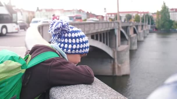 A child stands on the embankment of a river in the city. Looks at the water.