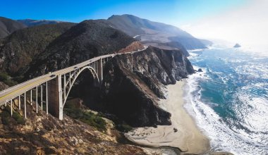 Aerial panoramic view of historic Bixby Creek Bridge along world famous Pacific Coast Highway 1 in summer sunny day , Monterey County, California, USA, shot from dron