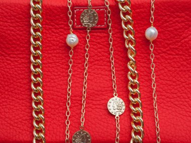 Two women`s gold necklaces on female red leather cosmetic bag background. Close-up shot