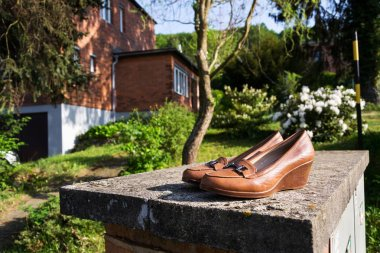 Old vintage shoes with typified red brick family Bata house in background, Zlin, Moravia, Czech Republic, sunny summer day
