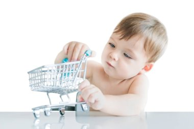 Cute small blond boy plays with a little shopping trolley at the table on a white background