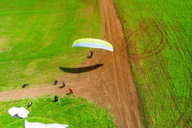 Top view of the man takes off from the field on a paraglider