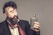 Fotografie Feuchtfröhliche bärtiger Mann in Anzug spricht mit einer Flasche Alkohol auf braunem Hintergrund