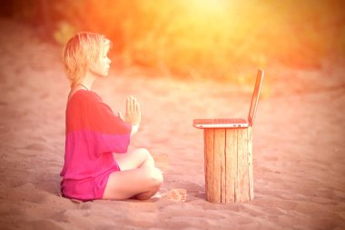 Girl blonde teenager in red blouse meditating in front of a laptop at the beach