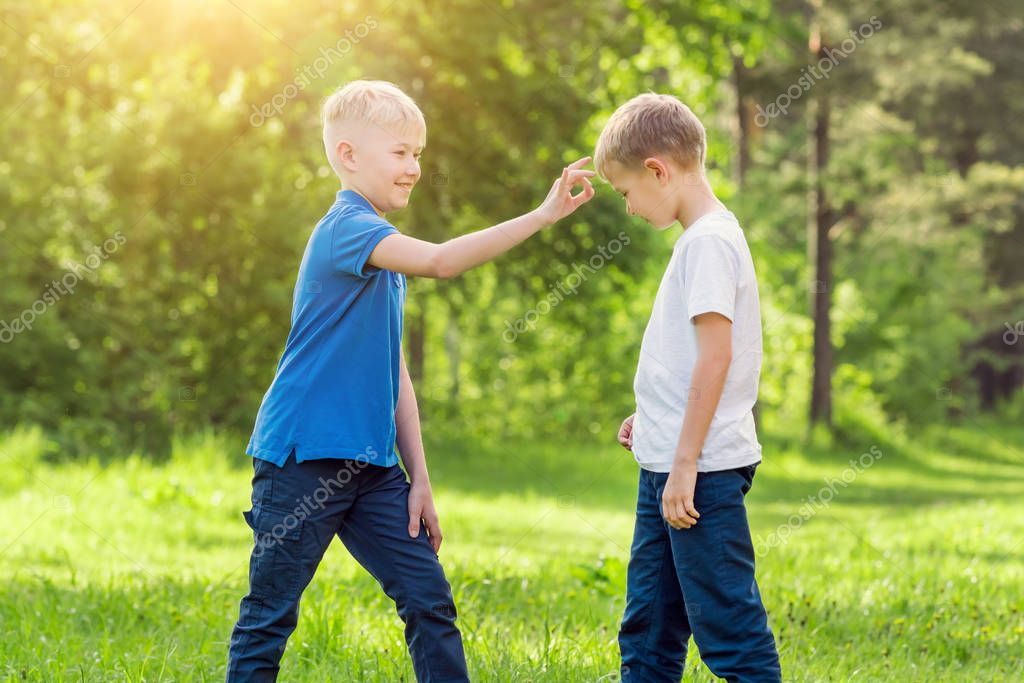Blond boy click his finger on the forehead of his friend in a sunny park