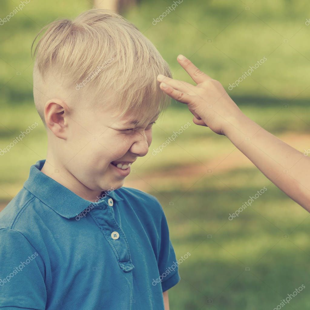 Boy in blue t-shirt waiting for a flick of finger in the forehead