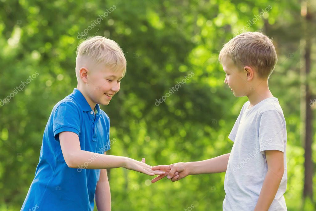 Two  blond  boys play rock paper scissors in the park