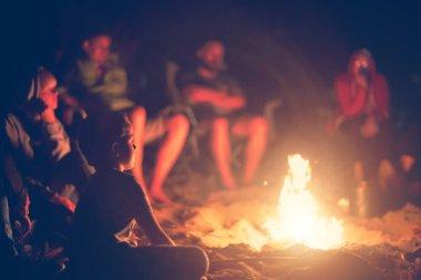 Gece kampı. Kamp ateşinin yanında oturan ve ateşe bakan çocuk