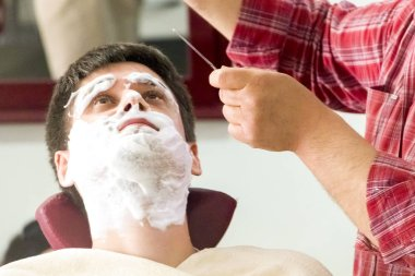 Young man in the barber shop preparing to shave.