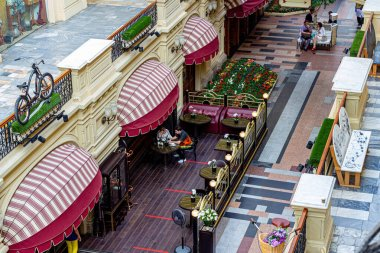 Moscow, Russia, 07.10.2020. Top view of the line of the Moscow GUM store with visitors strolling and resting in the cafe