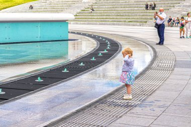Moscow, Russia, 08.07.2020. A little girl looks at water jets in a cascading light-dynamic fountain, in the business district of Moscow-city