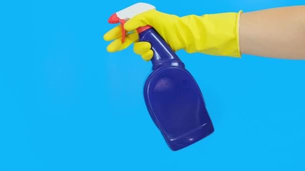 Hand in Hand ein gelber Gummihandschuh, der eine blaue Reinigungssprayflasche in Nahaufnahme hält und benutzt, blauer Hintergrund. Wasch-, Reinigungs- und Wischkonzept