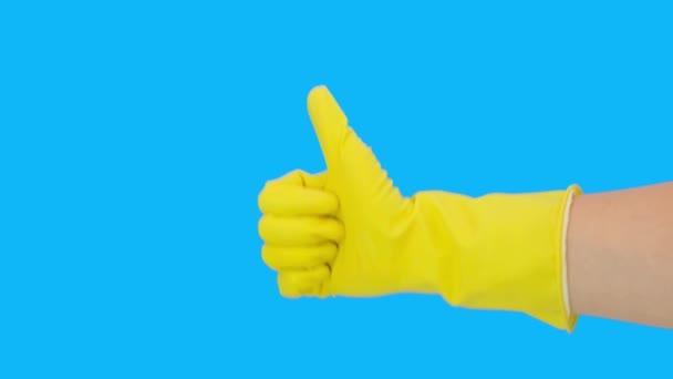 Nahaufnahme der weiblichen Hand in gelbem schützenden Latex-Gummihandschuh, Daumen hoch Zeichen, Geste vor blauem Hintergrund, Hausarbeit Konzept