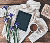 Flat lay shot of sweater, iris flowers, cup of coffee, gift box and digital tablet on wooden desk