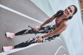 bruneta žena odpočívá na stadionu běžecké dráhy a při pohledu na fotoaparát s úsměvem