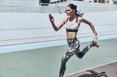 atlet žena v sportovní oblečení, běhání na stadionu