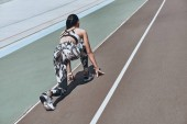 Fotografie rear view of young woman in sports clothing standing on start line on running track stadium