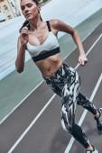 Fotografie sportliche Frau in Sportbekleidung Joggen auf Laufstrecke Stadion