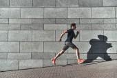pohledný mladý muž v sportovní oblečení, běží v městě ulici u kamenné zdi