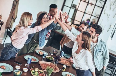 happy friends giving each other high-five and smiling while having dinner party at table