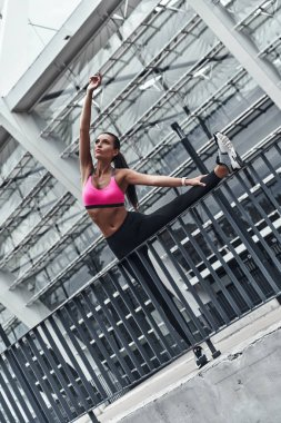 full length of sportive woman stretching legs and hands outdoors at railings of stadium