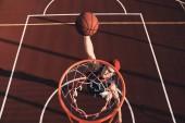 Fotografie pohled shora mladíka v sportovní oblečení bodování slam dunk při hraní basketbalu venku